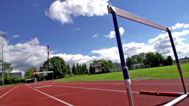 HD Super Slow-Mo: Young man running over hurdles