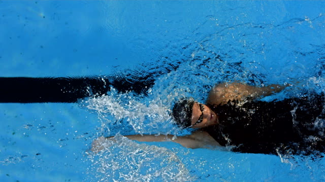 HD Super Slow-Mo: Young Woman Swimming Backstroke