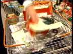 Supermarkets report on attempts to reduce packaging waste ENGLAND London INT Reporter to camera as demonstrates packaging on average supermarket...