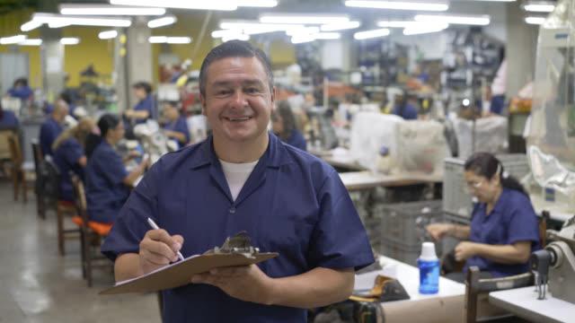 Toezichthouder in een fabriek van de schoen die aantekeningen maakt de camera kijken