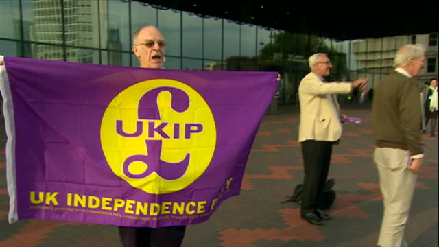 UKIP supporter holding up party flag outside the 2014 Conservative Party Annual Conference
