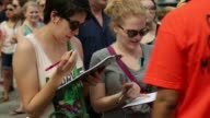 Supporters fill up forms for purchasing official campaign merchandise prior to Democratic presidential hopeful and former US Secretary of State...