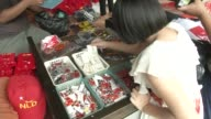 Supporters of Myanmar opposition leader Aung San Suu Kyi purchase souvenirs at outside the National League of Democracy headquarters in Yangon The...