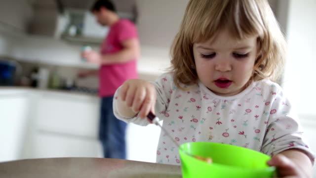 Supporto padre bambina mangia la prima colazione