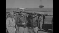 Supreme Commander Southwest Pacific Area General Douglas MacArthur walking toward probably officers on what looks like an airfield he salutes / MS...