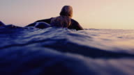 Surf girl paddles by camera on a California summer evening on surfboard shot in slow motion at sunset.
