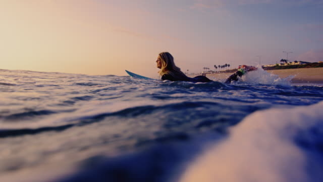 Surf girl runs out into the California ocean on surfboard shot in slow motion at sunset.