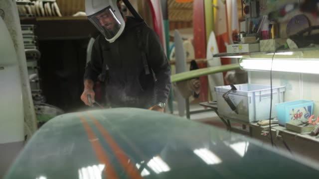 Surfboard shaper blowing fibreglass dust off of surfboard surface
