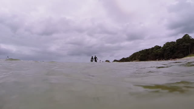 A surfer couple with their boards getting into the water, slow motion