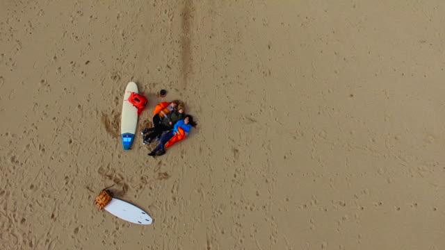 Surfer girls relaxing on the beach 4K