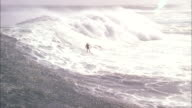 Surfer rides huge waves off Durban coast. Available in HD.