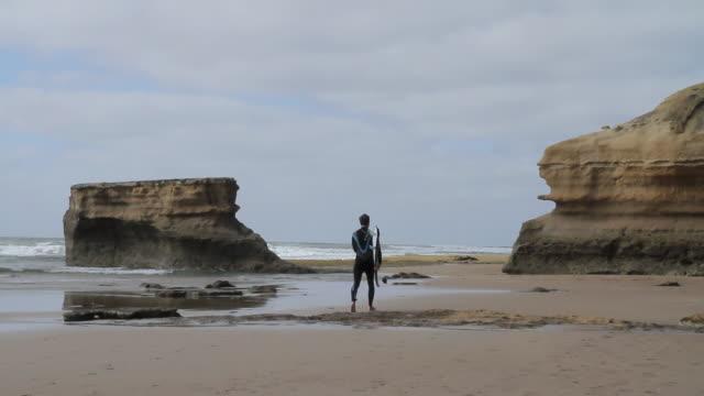MS Surfer walking along beach towards waves at Jan Juc beach / Jan Juc, Victoria, Australia