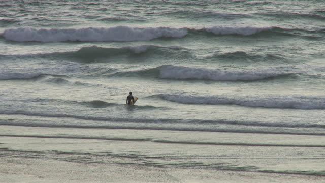 MS Surfer walking into surf / Cap de l'Homy, Aquitaine, France