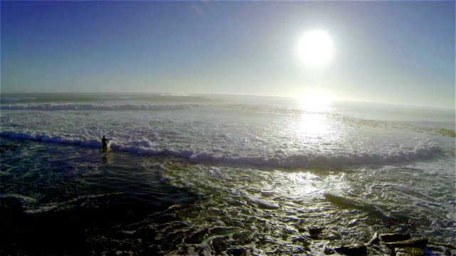 SLO MO of surfer walking into the ocean across the white water/ Western Cape/ South Africa