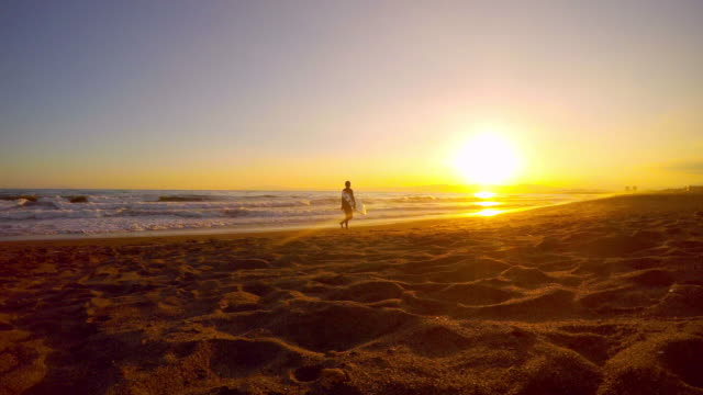 A surfer walking on the beach at sunset -4K-