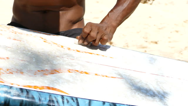 surfer waxing board before surfing