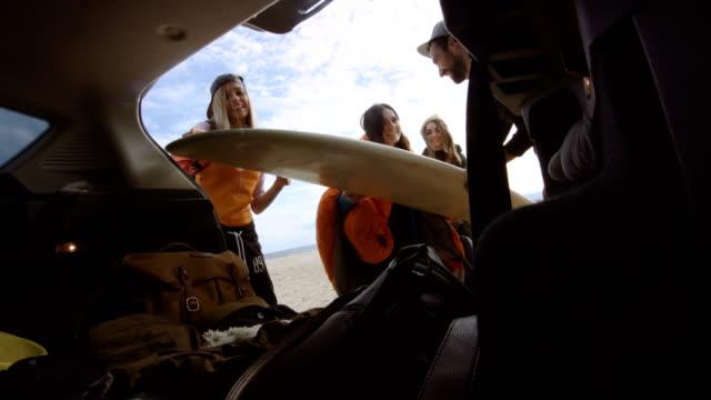 Surfers unpacking car trunk 4K