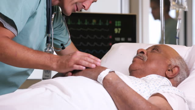 CU TD Surgeon Talking to Senior Patient in Hospital Bed / Richmond, Virginia, USA