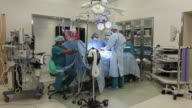 WS Surgical team performing surgical procedure in operating room / Seattle, Washington, USA