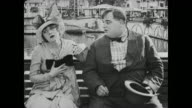 Surprised Fatty Arbuckle slides up to sick woman on bench and is concerned she will vomit in his hat