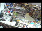 / surveillance video of thief walking into convenience store / man wearing hoodie and sunglasses pulls out small knife and asks clerk for all the...