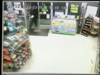 / surveillance video robbers come into convenience store demand money female clerk hands over the cash / one robber wants more and comes behind the...