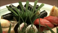 A sushi item platter uses garnishes for an artistic effect.