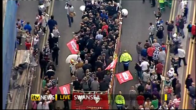 Swansea City promoted to Premier League AIR VIEWs / AERIALs Swansea City team waving to crowds from opentop bus during parade to celebrate promotion...
