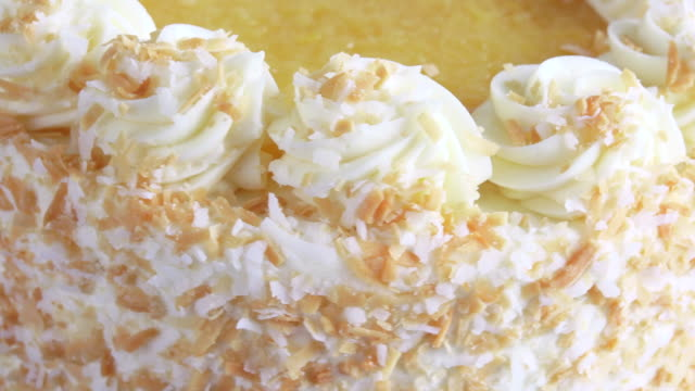 Sweet Pastry Food: Pina Colada Cake slowly turning in display. Beautiful icing decoration with yellow and yellowish color.