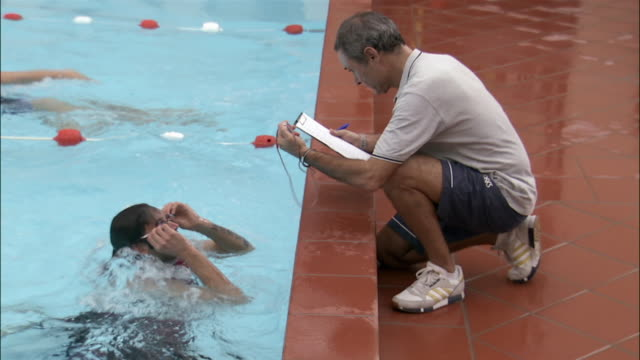 Swimmer doing timed practice with trainer