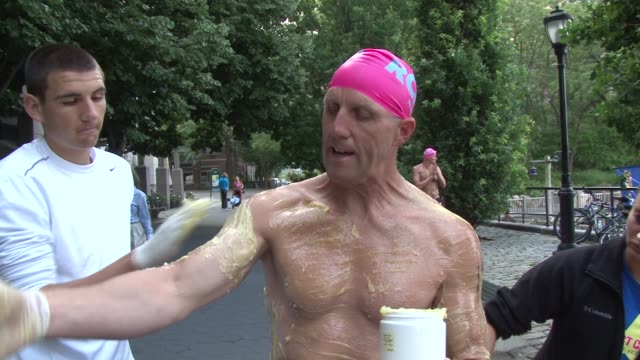 Swimmers from around the world challenge themselves in the annual 30 mile circuit of Manhattan Island Prerace grease up to help with cold water