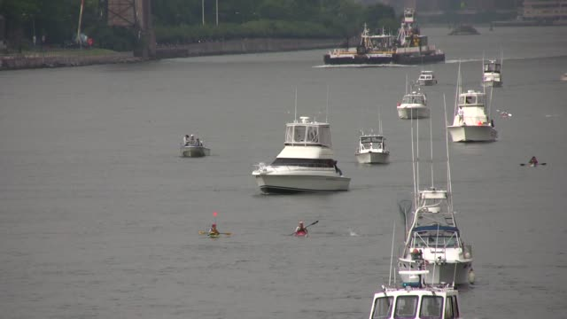 Swimmers from around the world challenge themselves in the annual 30 mile circuit of Manhattan Island Swimmers with boat escorts head up East River