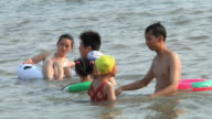 MS PAN Swimmers in water with floating toys / Xiamen, Fujian, China