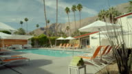 WS TS swimming pool at desert resort hotel with lounge chairs, white umbrellas and a view of the San Jacinto mountains and palm trees