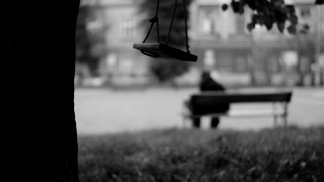 Swinging swing, man sitting on a bench in the background