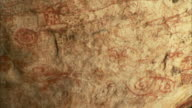 Swirling written symbols cover a cave wall at Pedra Pintada Cave in Brazil. Available in HD.