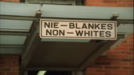 Swish pan and zoom out of signs above the entrances of the Apartheid Museum, in Afrikaans and English, one saying 'Whites' the other 'Non-Whites'