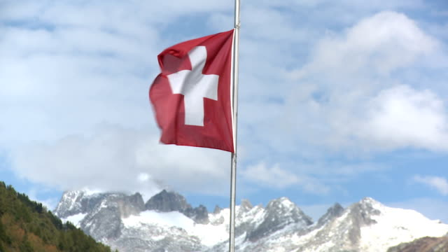 Swiss flag flutters in the wind, mountain range in background.