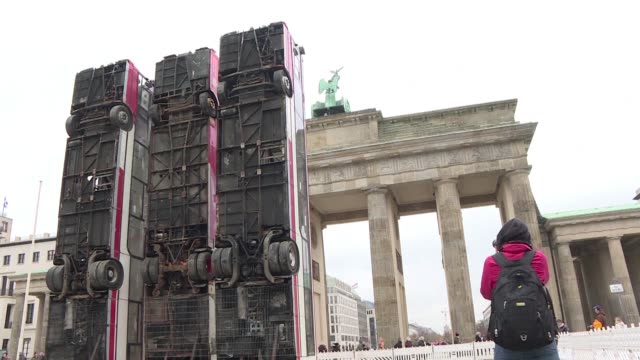 A Syrian German artist places three vertical buses in front of Berlin's Brandenburg Gate to recall the barricades used by Aleppo's civilians during...