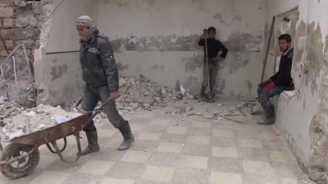 Syrian men reconstruct a school destroyed by Russian airstrikes the day before in Aleppo Syria on January 14 2016 Three children were killed and...