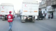 Syrian Red Crescent trucks carrying humanitarian aid sent by United Nations arrive East Ghouta Region of Damascus Syria on on June 29 2016