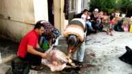 Syrian refugee Husin Lok helps family members cut the meat off a sacrificial sheep at their home during EidalAdha celebrations on September 01 2017...