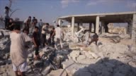 Syrians assessed the damage after reported airstrikes in the town of Jarjanaz in Syria's Idlib province Wednesday