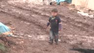Syrians evacuated from eastern Aleppo due to Assad regime and its supporter foreign terrorists attacks on civilians are seen on a muddy place as they...