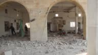 Syrians inspect the rubble of Abu Bakr alSiddiq mosque and destroyed buildings following the ongoing airstrikes of Syrian regime warplanes in...