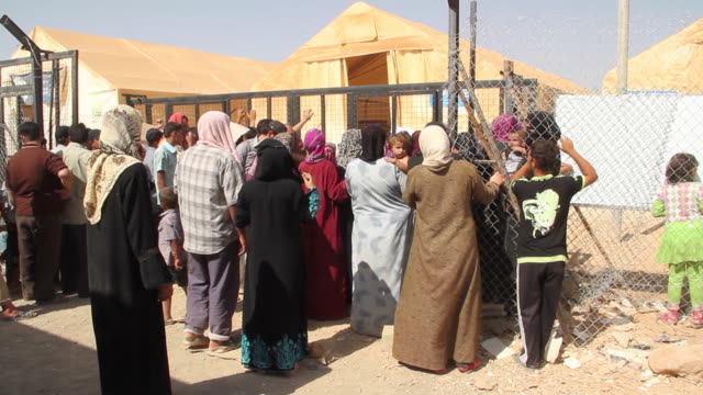 Syrians line up for food and supplies at the Zataari Refugee Camp in Jordan