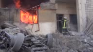 Syrians search for survivors and firefighters try to extinguish fire at buildings after Assad Regime forces carried out airstrikes on a residential...