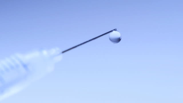 Syringe close-up, liquid dripping slowly, drug abuse concept (HD720p)