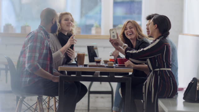 WS. Table of friends chat in local coffee shop and snap pictures of drinks with smartphone.