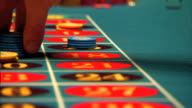 Table w/ red black circled numbers male fingers taking away blue chips others placing bets w/ yellow chips Gambling gaming betting